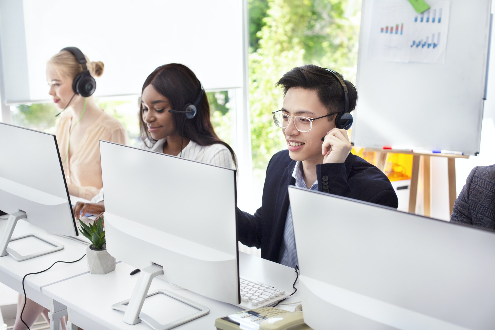 Team of helpline operators with headsets consulting clients at call center